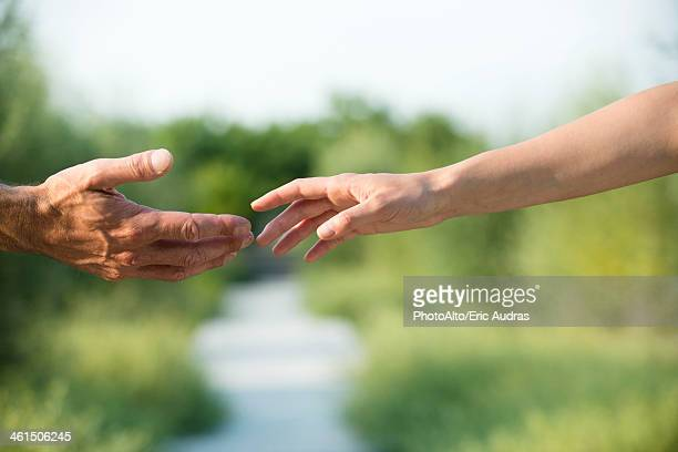 Man and woman reaching out to shake hands