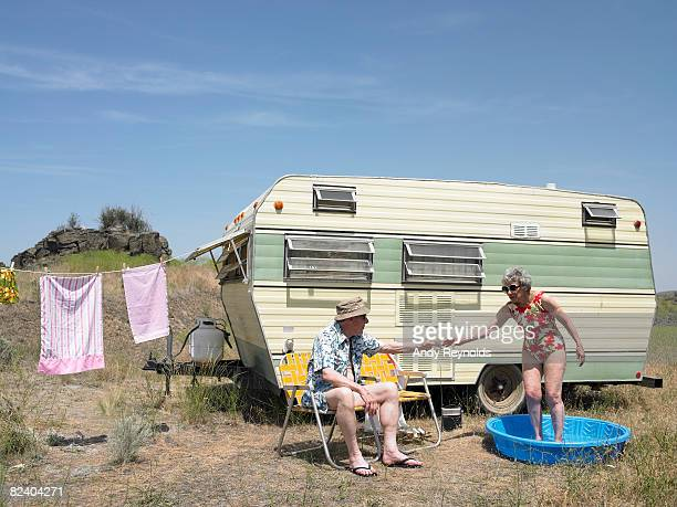 man and woman relaxing next to trailer