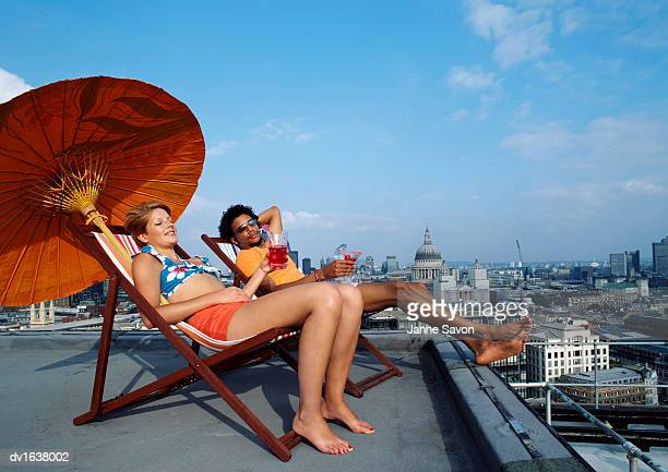 A Man and Woman Relaxing on Deck Chairs on a Roof with St Pauls Catherdral in the Background