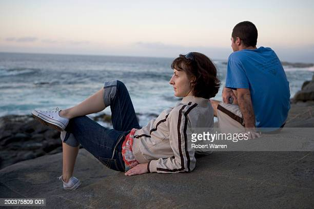 Man and woman relaxing on rock, looking out to sea, sunset, side view