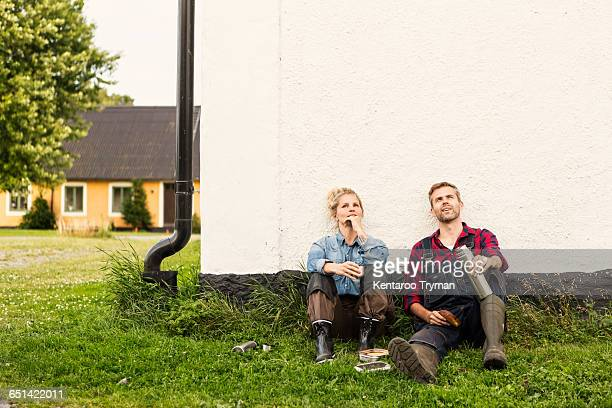 Man and woman relaxing while looking up against house