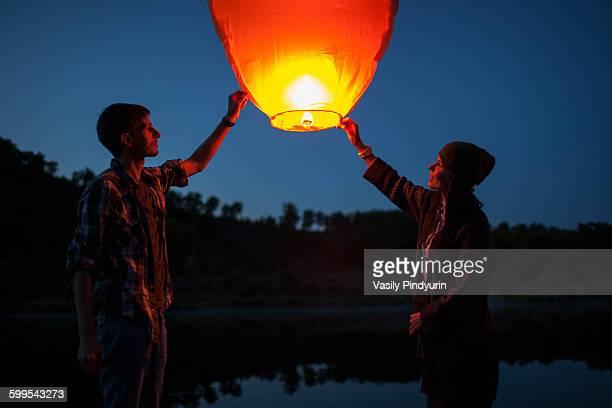 Man and woman releasing paper lanterns at lakeshore
