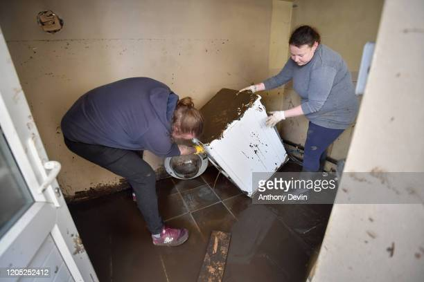 A man and woman remove a flooded washing machine as residents begin clearing up following severe flooding beside the River Calder on February 10 2020...
