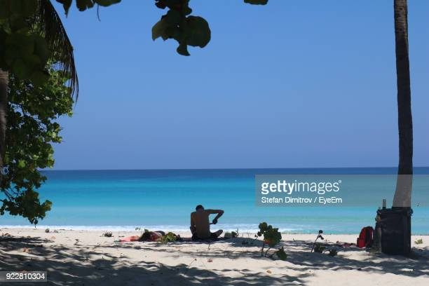 Man And Woman Resting At Beach Against Clear Blue Sky