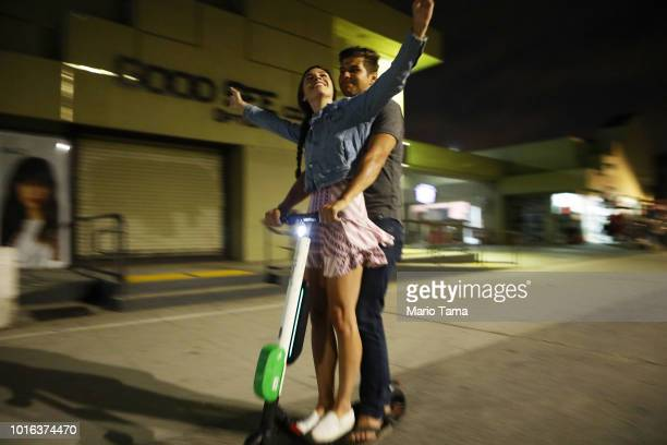 A man and woman ride a shared dockless electric scooter along Venice Beach on August 13 2018 in Los Angeles California Shared escooter startups Bird...
