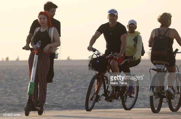 A man and woman ride a shared dockless electric scooter next to bicycles along Venice Beach on August 13 2018 in Los Angeles California Shared...
