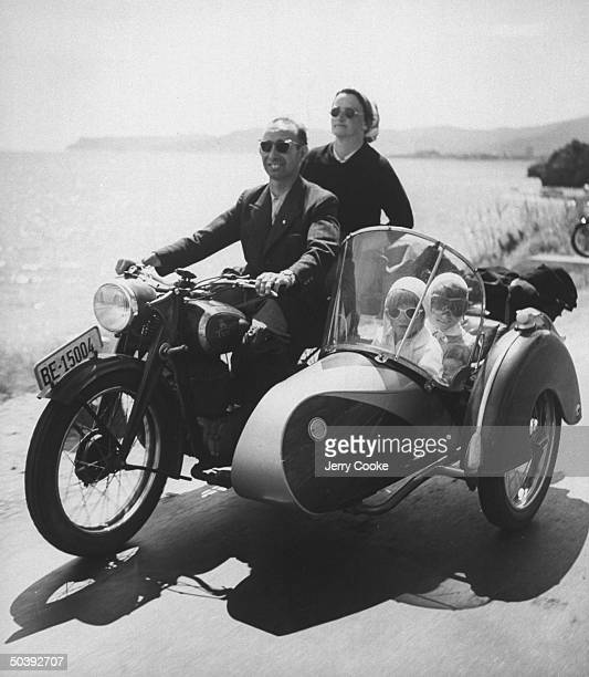 Man and woman riding a motorcycle with three children tucked into the attached side car on a family trip in Italy, July 1954.