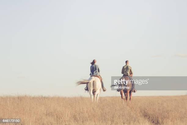 Man And Woman Riding Away On Horseback