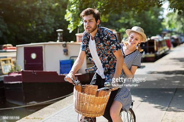Man and woman riding bicycle on canal towpath