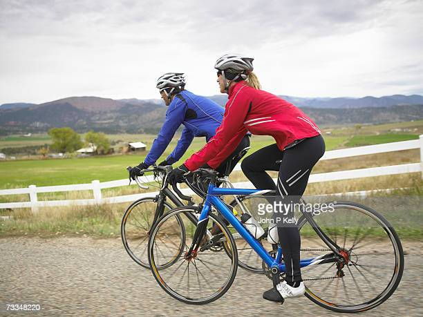 man and woman riding bicycle on rural road, side view - コロラド州 ニューキャッスル ストックフォトと画像