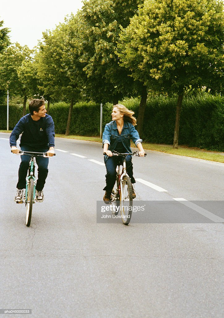 Man and woman riding bikes side by side, looking at each other, full length, front view : Stockfoto