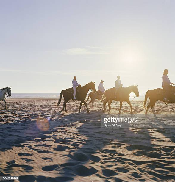 Man and woman riding horses on beach with children (7-11), side view