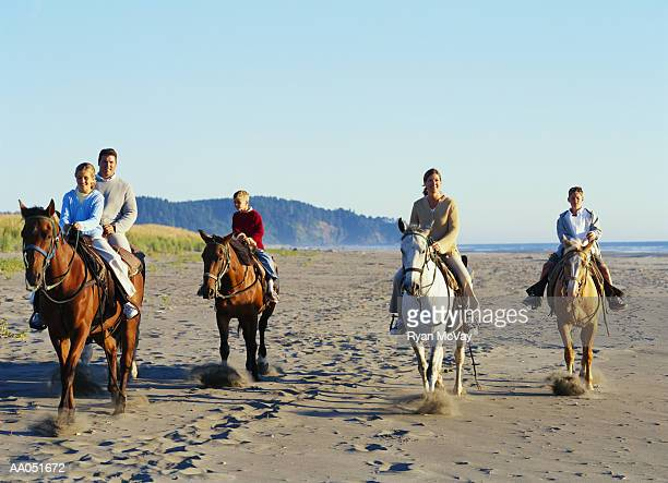 Man and woman riding horses on beach with three children (7-11)