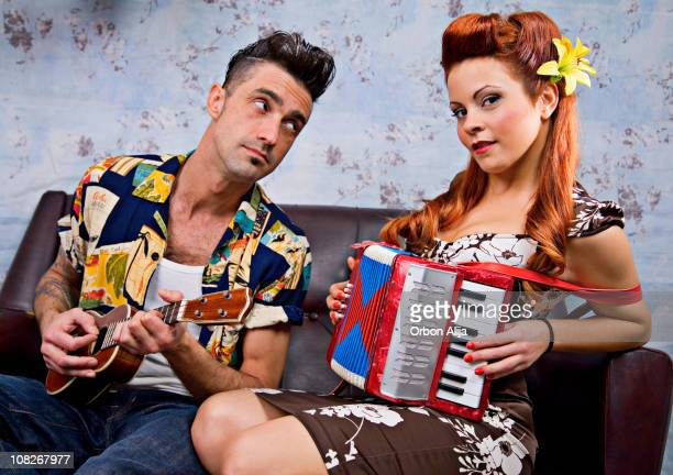 man and woman rockabilly couple sitting on couch playing instruments - pinup stockfoto's en -beelden