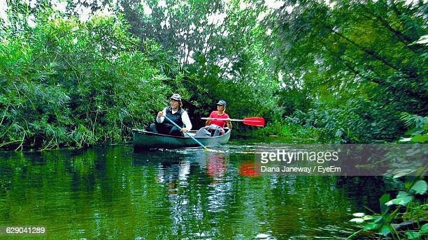 Man And Woman Rowing Boat In River