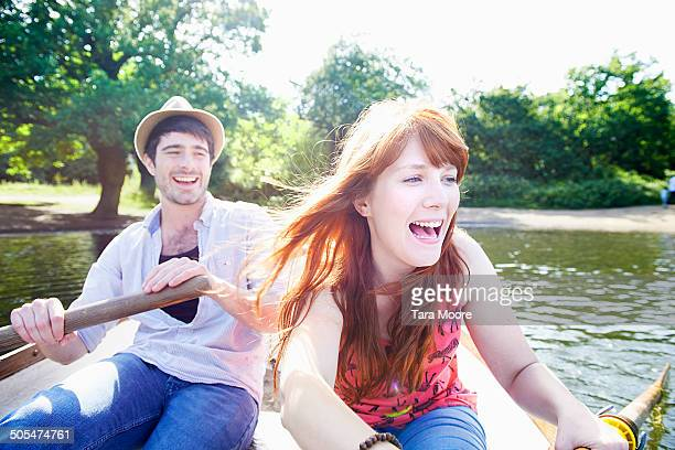 man and woman rowing in boat on lake