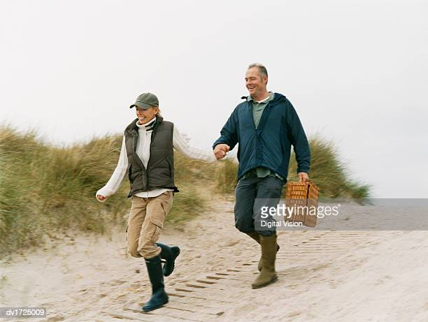 Man and Woman Run Down a Sand Dune Holding Hands