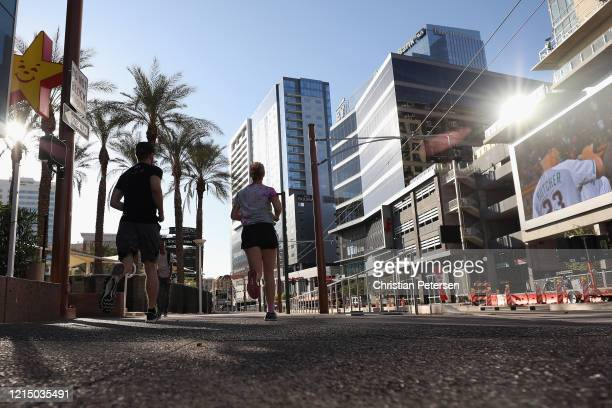Man and woman run through downtown on March 26, 2020 in Phoenix, Arizona. The Coronavirus pandemic has spread to many countries across the world,...
