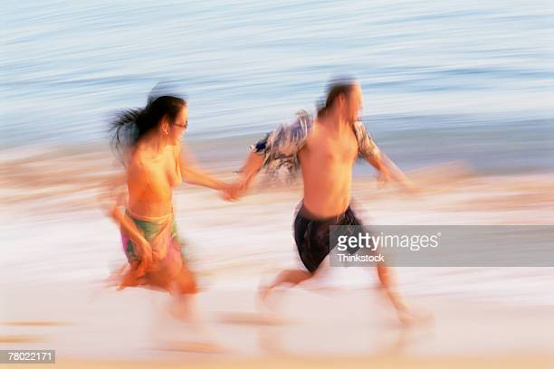 man and woman running along beach - thinkstock stock photos and pictures