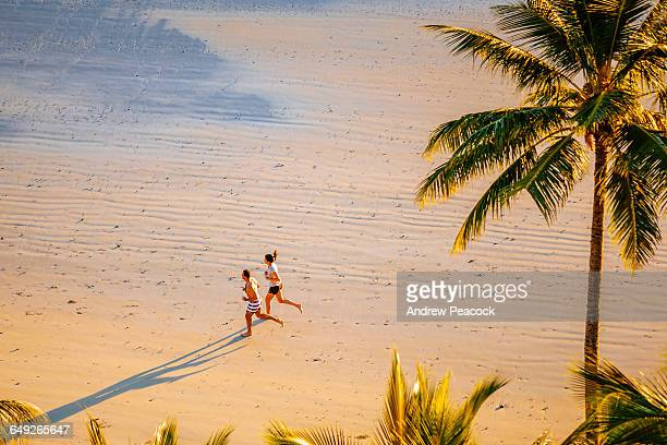 A man and woman running Catseye Beach