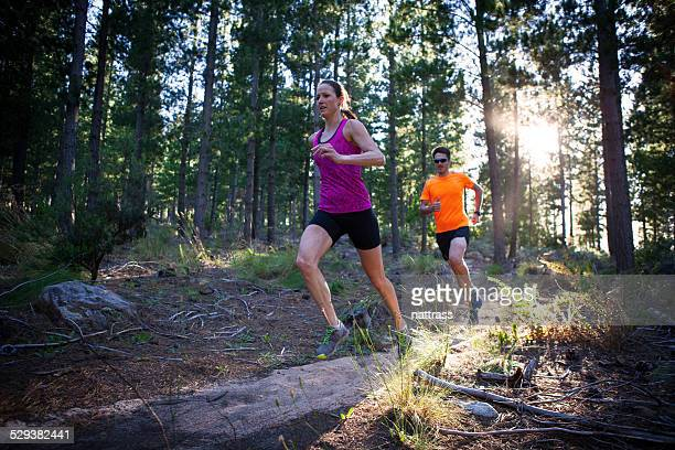 man and woman running in the forest early morning - cross country running stock pictures, royalty-free photos & images