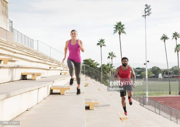 Man and woman running on bleachers