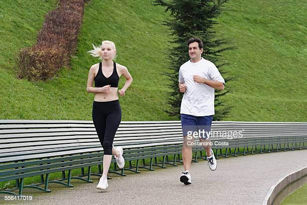 man and woman running on pathway beside lake - next to stock pictures, royalty-free photos & images