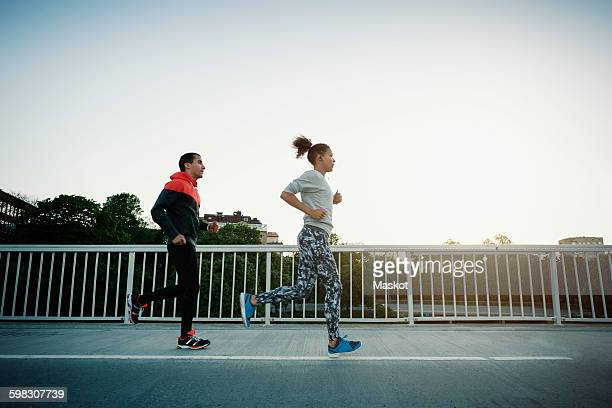 Man and woman running on sidewalk against clear sky