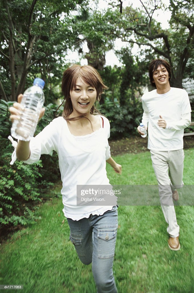 Man and Woman Running Outdoors, Woman Holding a Water Bottle : Stock Photo
