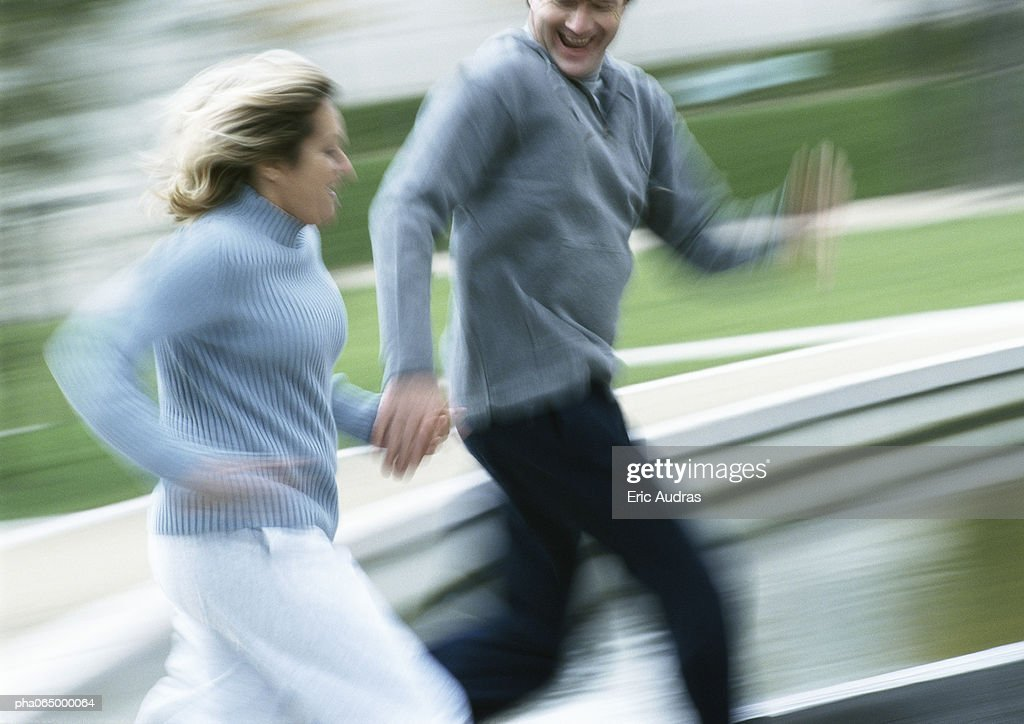 Man and woman running together outside, blurred. : Stockfoto