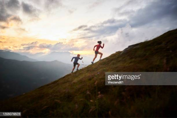 man and woman running uphill in the mountains - uphill stock pictures, royalty-free photos & images