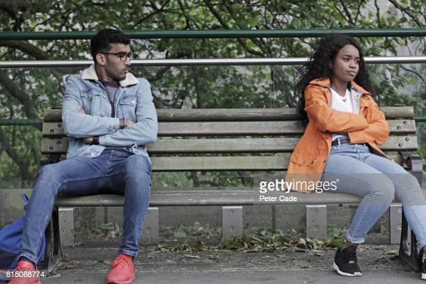 Man and woman sat at opposite ends of bench, not happy