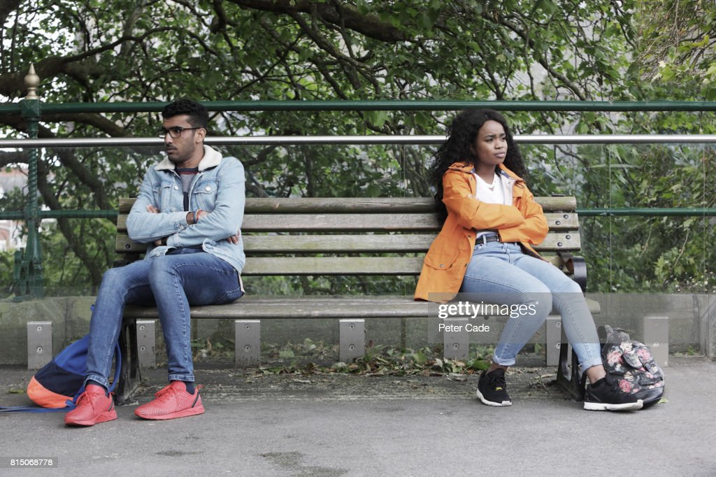 Man and woman sat at opposite ends of bench, not happy : Stock Photo
