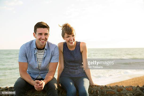 man and woman sat on wall laughing. - casal heterossexual - fotografias e filmes do acervo