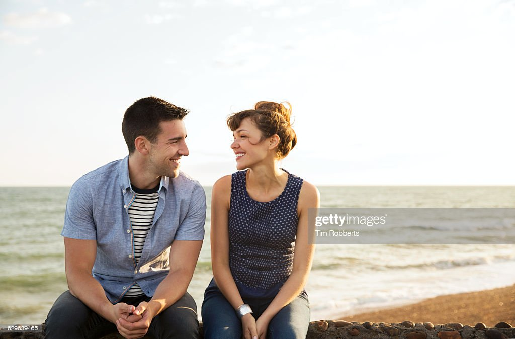 Man and woman sat on wall together : Stock Photo
