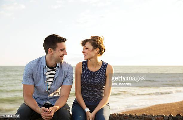 man and woman sat on wall together - dating stock-fotos und bilder