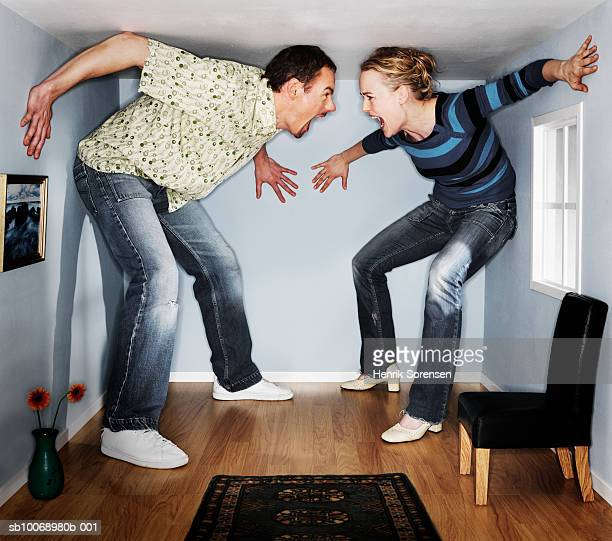 man and woman screaming at each other in small living room - casal heterossexual imagens e fotografias de stock