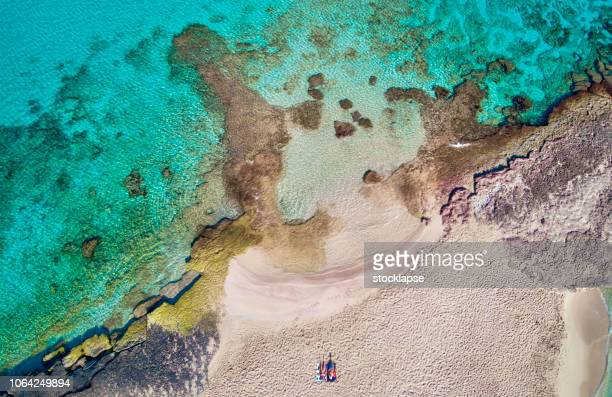 man and woman seated in the sand at cala conta - coral sea stock photos and pictures