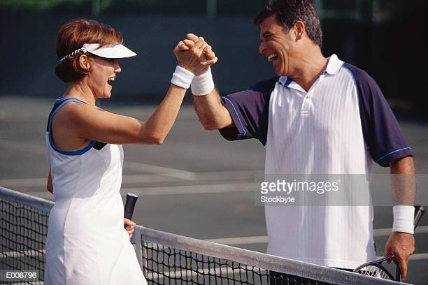 Man and woman shaking hands after tennis match