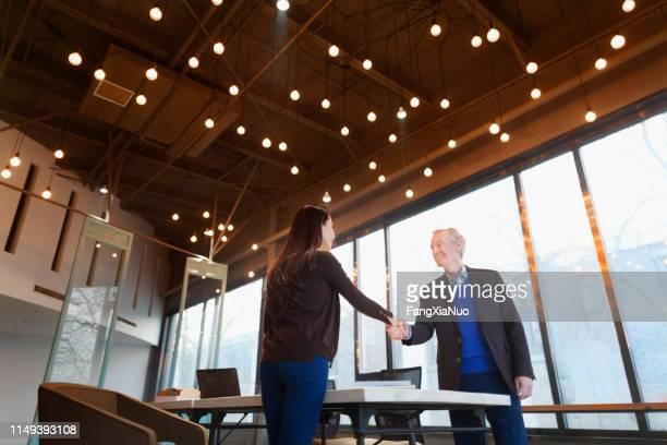 デザインオフィスで握手する男と女 - 後任 ストックフォトと画像