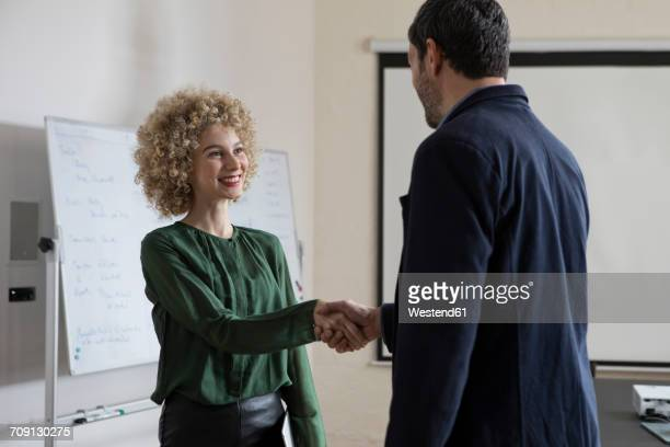 Man and woman shaking hands in office