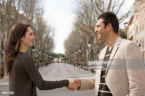 Man and woman shaking hands outdoors in city