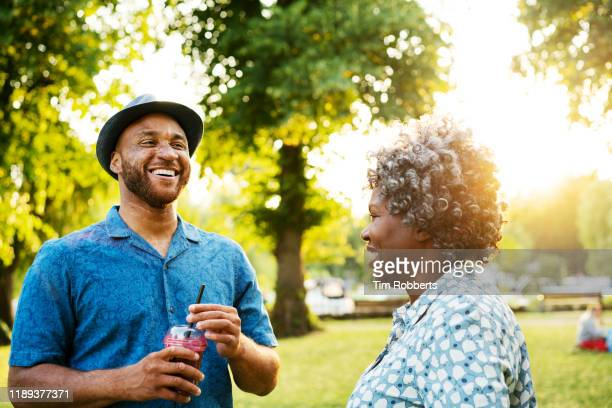 man and woman sharing a joke in park - discussion stock pictures, royalty-free photos & images