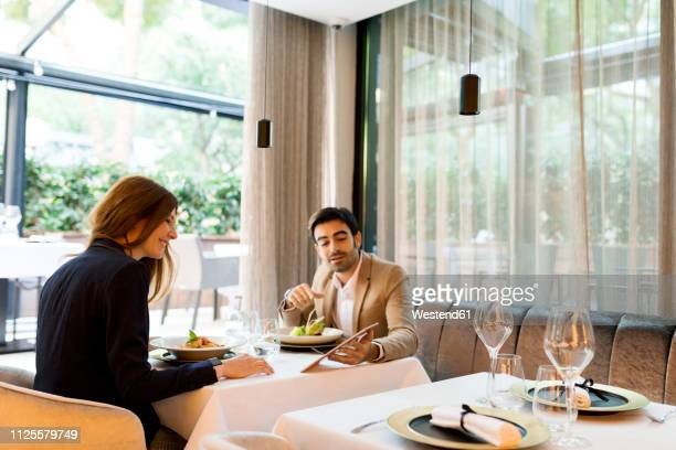 man and woman sharing a tablet in a restaurant - elegance stock pictures, royalty-free photos & images