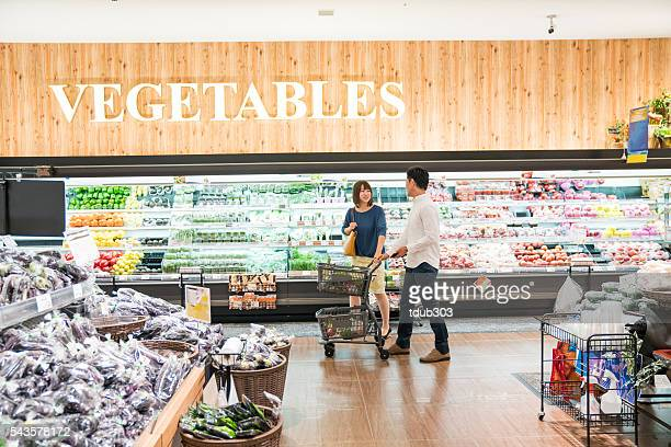 Man and woman shopping in a supermarket produce section
