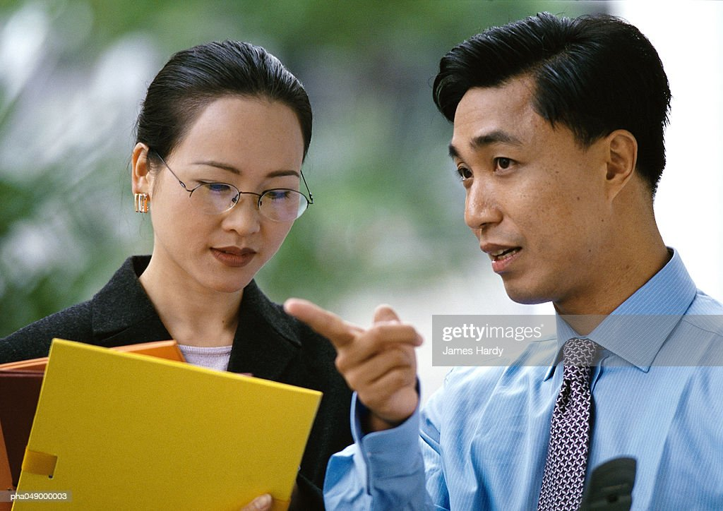 Man and woman side by side, woman holding folders, head and shoulders : Stockfoto