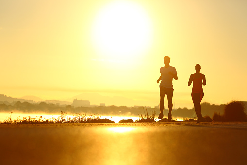 Man and woman silhouettes running at sunrise 1051175288
