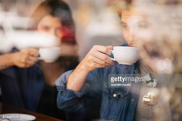 Man and Woman Sipping Their Coffee in Cafe