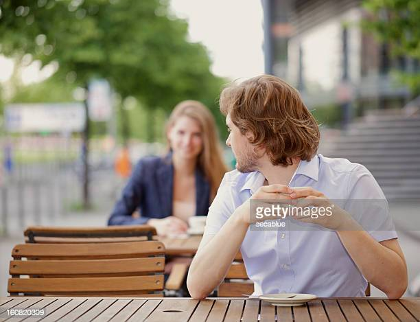 Man and Woman sit at cafe