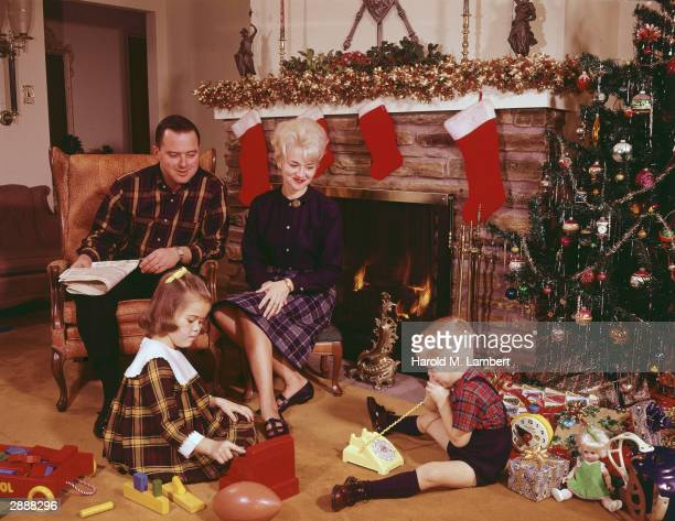 A man and woman sit by a fireplace hung with stockings as a young boy and girl play with their new presents by a Christmas tree circa 1960